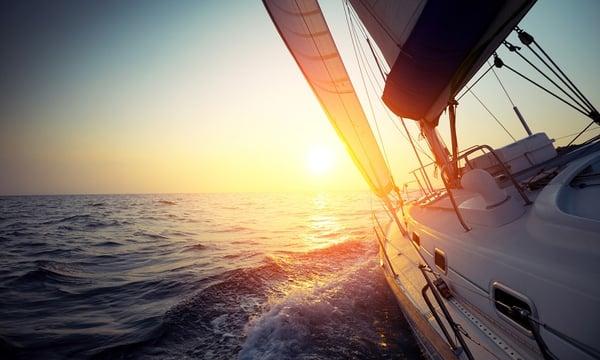 A boat sailing towards the horizon